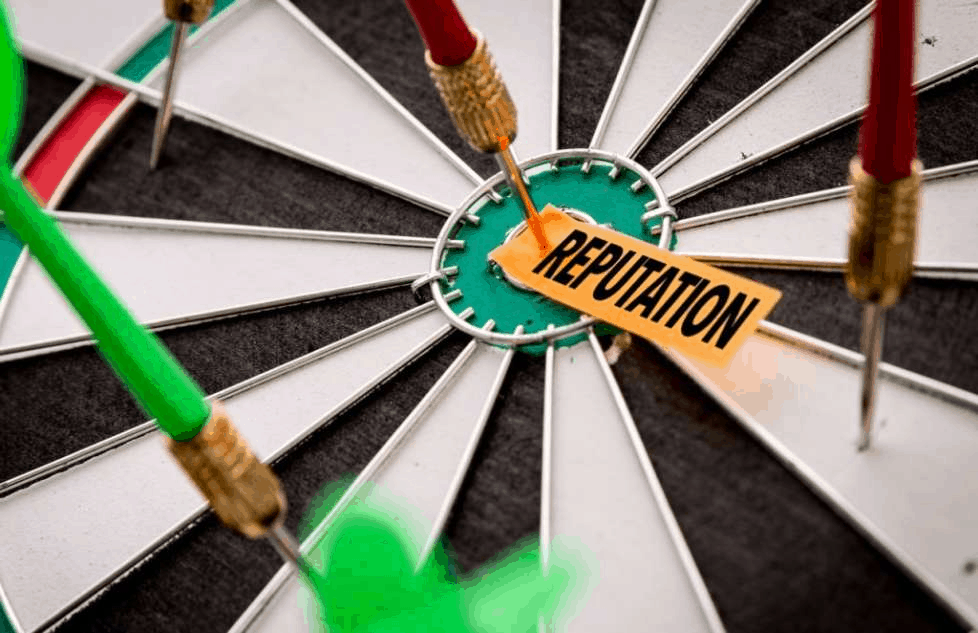 A dartboard with a tag saying 'reputation' pinned to the bullseye with a dart