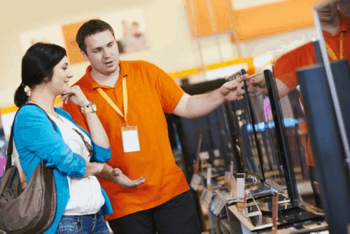 A man in an orange shirt with a lanyard pointing to monitors in a store with a woman listening with her head resting on her hand