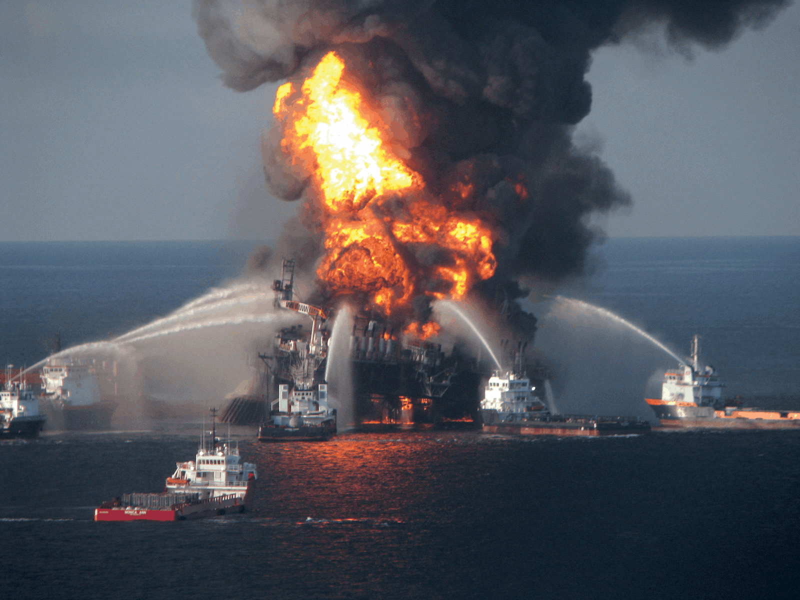 Image of BP Oil's Deepwater Horizon spill with a rig on fire at sea and shits spraying water onto the fire and black smoke