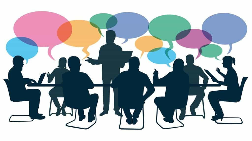 Silhouettes of people at a meeting with multi-coloured speech bubbles